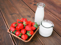 Fresh tasty strawberries. With bottle of milk over wooden background Royalty Free Stock Images