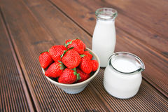 Fresh tasty strawberries. With bottle of milk over wooden background Stock Photo