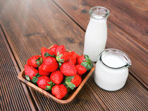 Fresh tasty strawberries. With bottle of milk over wooden background Stock Images