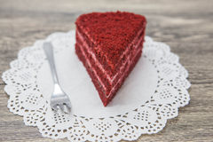 Fresh tasty sweet piece of  red velvet cake, on a white napkin and a dessert fork on a wooden background Royalty Free Stock Photo