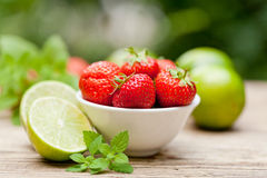 Fresh tasty sweet strawberries and green lime outdoor in summer Royalty Free Stock Photos