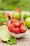 Fresh tasty sweet strawberries and green lime outdoor in summer Stock Image