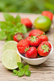 Fresh tasty sweet strawberries and green lime outdoor in summer Royalty Free Stock Photography