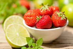 Fresh tasty sweet strawberries and green lime outdoor in summer Royalty Free Stock Images