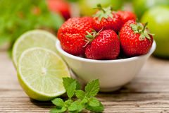 Fresh tasty sweet strawberries and green lime outdoor in summer Stock Images