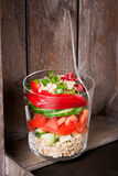 Fresh tasty vegetarian or vegan layer salad with tomatoes, cucumber, paprika, green onion and grain in a glass on a wooden backgro Stock Images