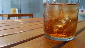 Fresh tea with ice cubes on the wooden. royalty free stock photos
