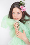 Fresh teenage girl impersonating spring. Beautiful stunning cute teenage girl portrait with roses in her hair and wearing a green gown as an impersonation of Royalty Free Stock Images