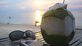 Fresh Thai Coconut cocktail, sunglasses, mobile phone lying on wooden table at Tropical Beach during amazing sunset. Travel vacation concept. Slow motion stock footage