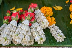 Fresh Thai style flower garlands made of white jasmine, crown flower, red rose and  yellow marigold selling on green banana leaves. In local market, selective Stock Images