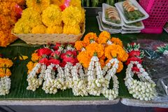 Fresh Thai style flower garlands made of white jasmine, crown flower, red rose and yellow marigold with betel nut tray royalty free stock images