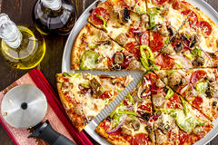 Fresh Thin Crust Supreme Pizza. Sliced fresh baked thin crust supreme pizza sitting on metal pan with containers of olive oil and red wine vinegar with striped stock photos