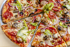 Fresh Thin Crust Supreme Pizza. Sliced thin crust supreme pizza sitting on metal pan made with fresh sausage, pepperoni, mushrooms, onions, green pepper and stock images