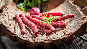 Fresh thin sausages on bark stock photography