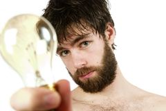 Fresh Thinking. A humor shot, of a young newly showered male, holding a light bulb, thinking up fresh new ideas Stock Image