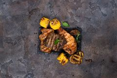 Fresh three types of grilled steak chicken, pork, beef on slate plate with herbs and grilled potatoes. On stone background with copy space, flat lay Royalty Free Stock Photos