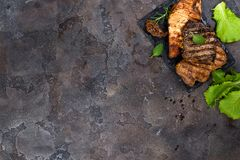 Fresh three types of grilled steak chicken, pork, beef on slate plate with herbs. On stone background with copy space, flat lay Stock Photo