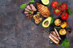 Fresh three types of grilled steak chicken, pork, beef on slate plate with herbs, tomato, avocado and grilled potatoes. On stone background with copy space Stock Photo