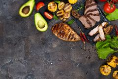 Fresh three types of grilled steak chicken, pork, beef on slate plate with herbs, tomato, avocado and grilled potatoes. On stone background with copy space Royalty Free Stock Photo
