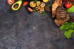 Fresh three types of grilled steak chicken, pork, beef on slate plate with herbs, tomato, avocado and grilled potatoes. On stone background with copy space Stock Photography