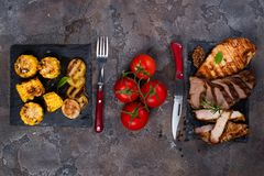 Fresh three types of grilled steak chicken, pork, beef on slate plate with herbs, tomato and grilled potatoes. On stone background with copy space, flat lay Stock Photography