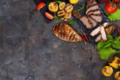 Fresh three types of grilled steak chicken, pork, beef on slate plate with herbs, tomato and grilled potatoes. On stone background with copy space, flat lay Royalty Free Stock Photos