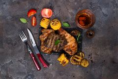 Fresh three types of grilled steak chicken, pork, beef on slate plate with herbs, tomato, juice and grilled potatoes. On stone background with copy space, flat Royalty Free Stock Photography