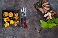 Fresh three types of grilled steak chicken, pork, beef on slate plate with spinach and grilled potatoes. On stone background with copy space, flat lay Stock Image