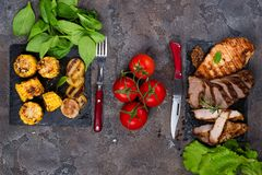 Fresh three types of grilled steak chicken, pork, beef on slate plate with spinach, tomato and grilled potatoes. On stone background with copy space, flat lay Stock Images