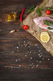 Fresh tilapia on dark wooden textured background with fresh rosemary and lemon. Culinary mediterranean seafood Royalty Free Stock Image