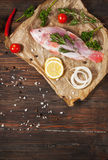 Fresh tilapia on dark wooden textured background with fresh rosemary and lemon. Culinary mediterranean seafood Royalty Free Stock Photography