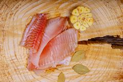 Fresh Tilapia with spice bay leaf and onion on cutting board stock photos