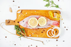 Fresh tilapia on white wooden textured background with fresh rosemary and lemon. Culinary mediterranean seafood Royalty Free Stock Image