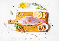 Fresh tilapia on white wooden textured background with fresh rosemary and lemon. Culinary mediterranean seafood. Stock Photos