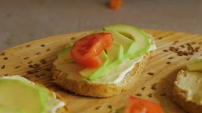 Avocado close up on the kitchen. Fresh toasts with avocado and tomatoes on wooden table stock footage