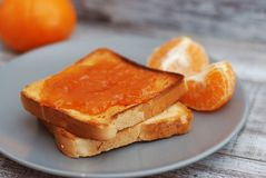 Fresh Toasts with Homemade Orange Jam on Gray Plate over Wooden Background. Fresh Toasts with Homemade Orange Jam on Gray Plate over Wood Stock Photo