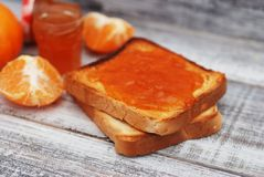 Fresh Toasts with Homemade Orange Jam on Gray Plate over Wooden Background. Fresh Toasts with Homemade Orange Jam on Gray Plate over Wood Royalty Free Stock Photos