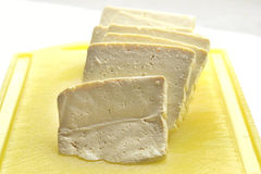 Fresh tofu slices. On a yellow plastic bredboard Royalty Free Stock Image