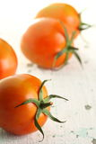 Ripe red tomatoes. On white wooden background Stock Image