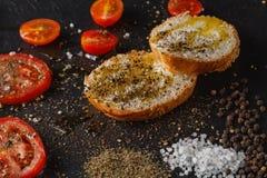 Fresh tomato on black plate with sea salt on background Stock Image