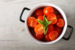 Fresh tomato in bowl. On complex background Royalty Free Stock Photography