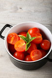 Fresh tomato in bowl. On complex background Royalty Free Stock Image