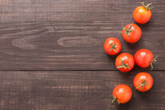 Fresh tomato on the brown wooden background. Top view Royalty Free Stock Image