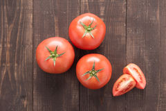 Fresh tomato on the brown wooden background. Top view Royalty Free Stock Images