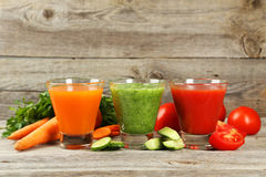 Fresh tomato, carrot and cucumber juice on grey wooden background. Stock Photos