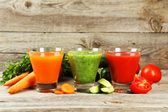 Fresh tomato, carrot and cucumber juice on grey wooden background. Fresh tomato, carrot and cucumber juice on grey wooden background Stock Photography