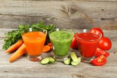 Fresh tomato, carrot and cucumber juice on  the grey wooden background Royalty Free Stock Photos