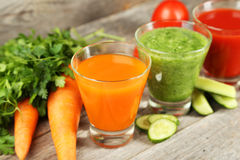 Fresh tomato. Carrot and cucumber juice on grey wooden background Royalty Free Stock Photos
