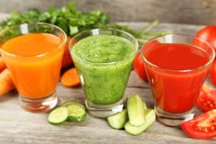 Fresh tomato, carrot and cucumber juice on wooden background Royalty Free Stock Photo