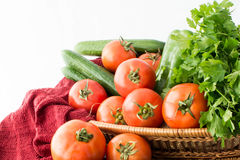 Fresh Tomato and cucumber basket. Basket with tomato cucumber and parsley on red towel Royalty Free Stock Image